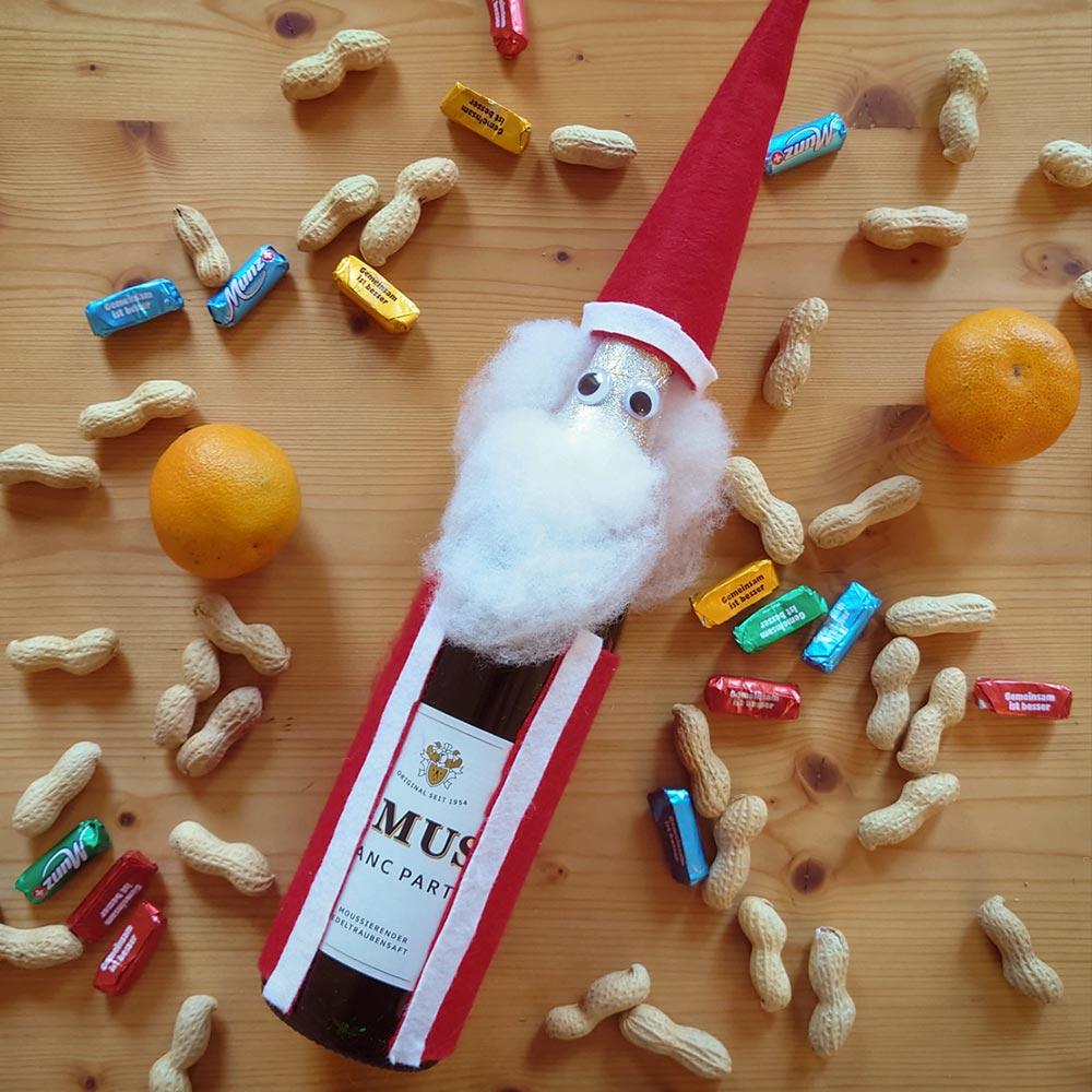 Eine Flasche Rimuss Party verkleidet als Weihnachtsmann / Samichlaus neben Erdnüssen, Mandarinen und Schokolade