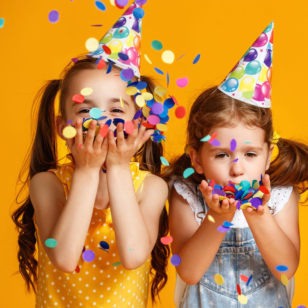 Zwei Mädchen blasen beim Kindergeburtstag Konfetti herum
