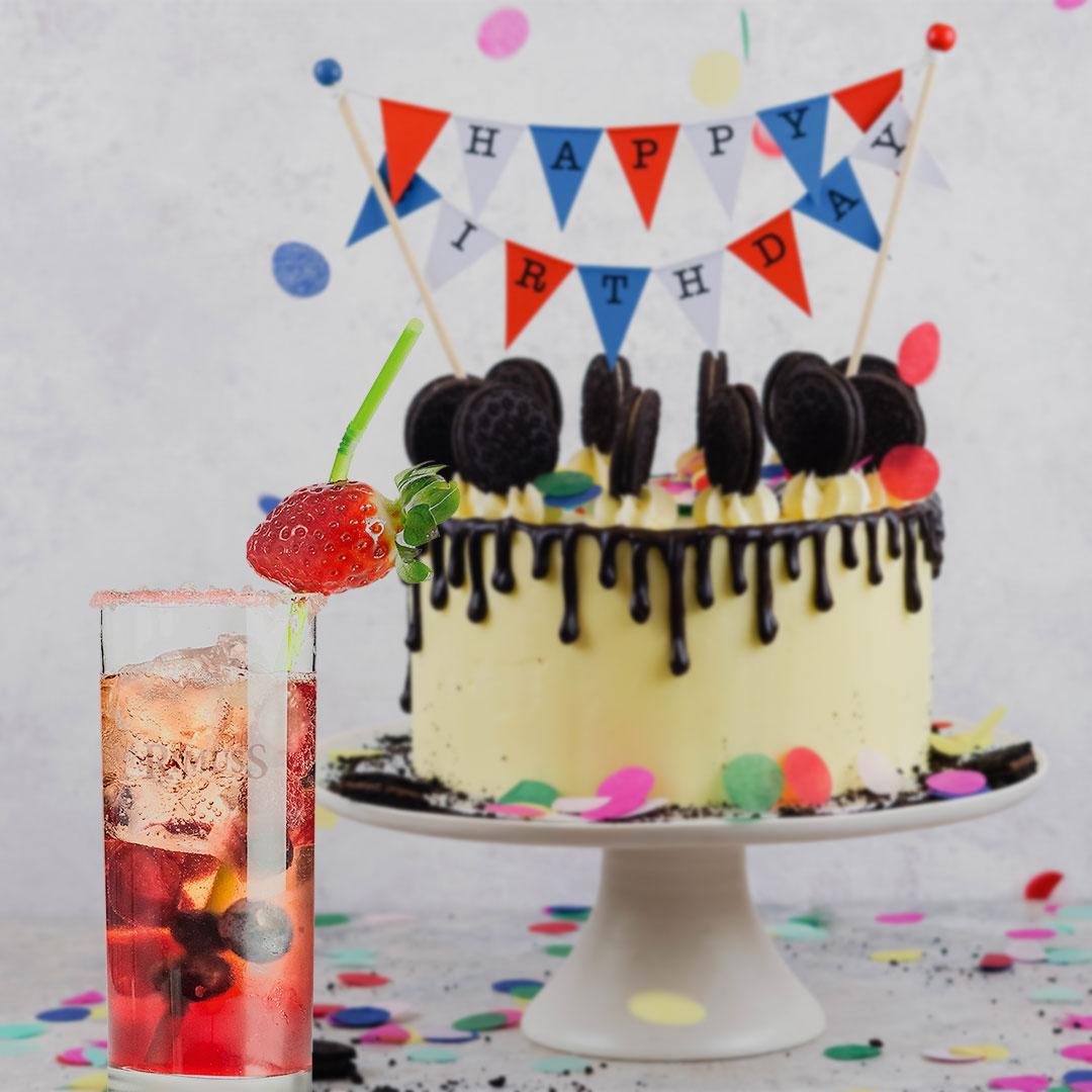 Ein toller Kindergeburtstags Drink / Mocktail mit verschiedenen Beeren steht vor einer Geburtstagstorte mit Konfetti