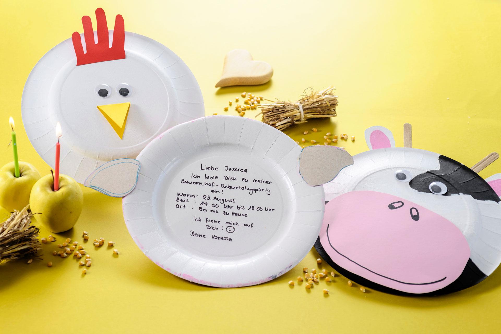 Eine Idee zum Basteln für die Einladung zum Kindergeburtstag: Lustige Tiergesichter aus Papptellern mit kleinen Strohballen und Äpfeln