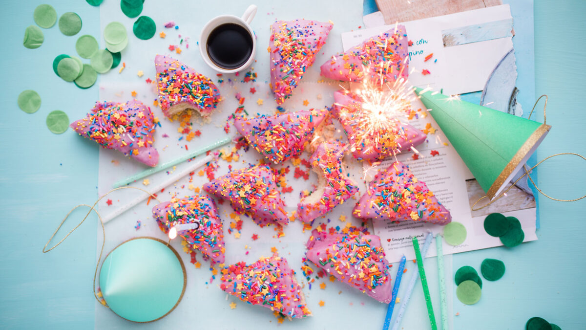 Ein Kindergeburtstag mit Partyhüten, Geburtstagskuchen, Kerzen, Konfetti, Malstiften und Bastelmaterial
