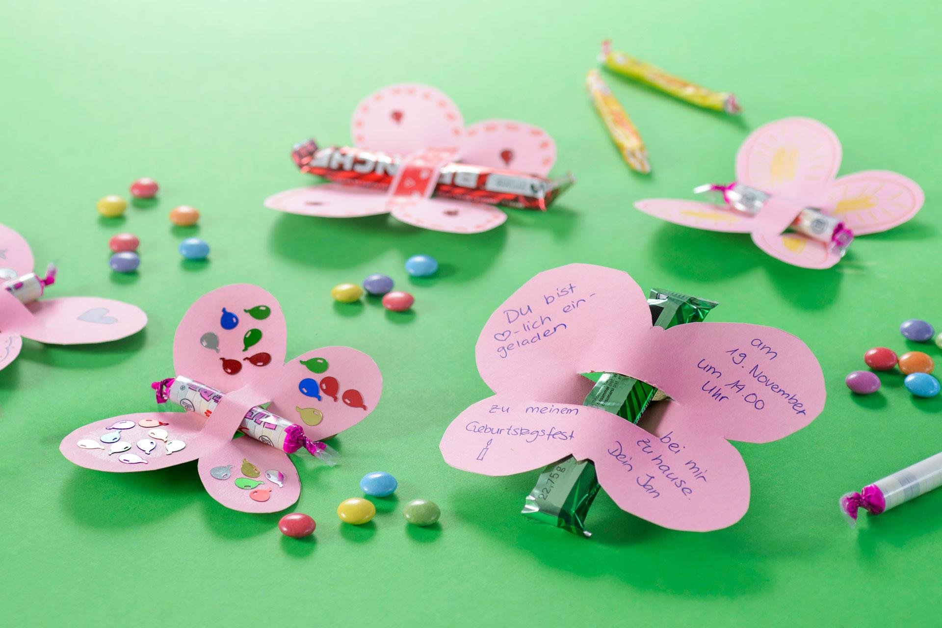 Ein tolle Idee zum Basteln einer Einladung zum Kindergeburtstag. Kleine Schmetterlinge mit Süssigkeiten als Körper