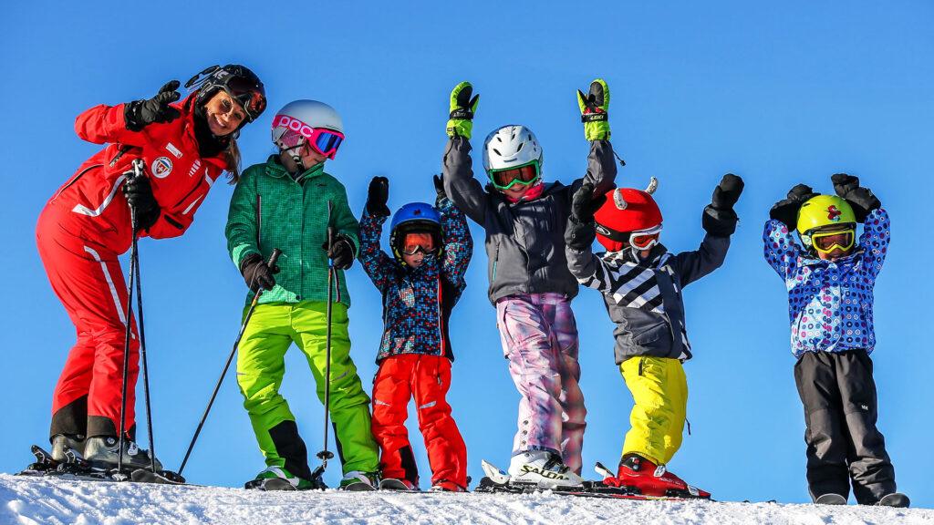 Meherer Kinder auf Skis und eine Skilehrerin auf einem verschneiten Hügeln freuen sich beim Kindergeburtstag in Grüsch Danusa