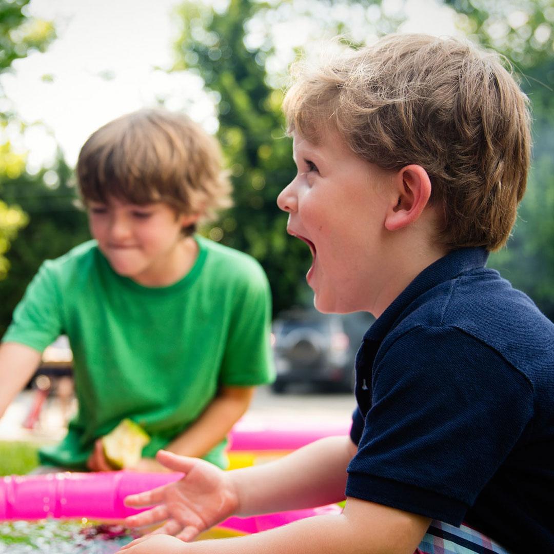 Zwei Kinder spielen ein Spiel bei einem Wasserbad beim Kindergeburtstag