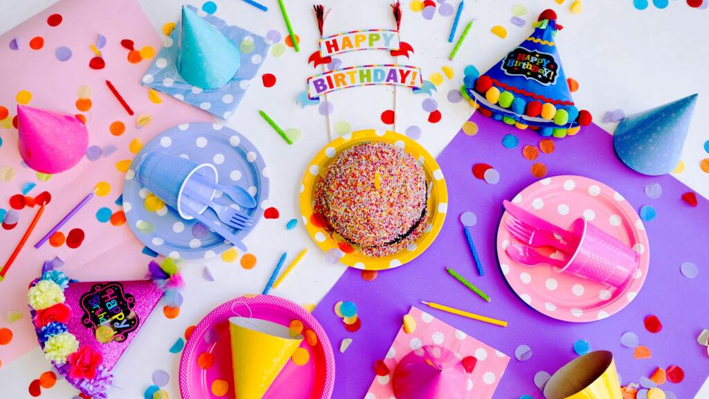 Ein unterhaltsamer Kindergeburtstag mit einem Kuchen Papptellern, Partyhüten, Konfetti und Kerzen