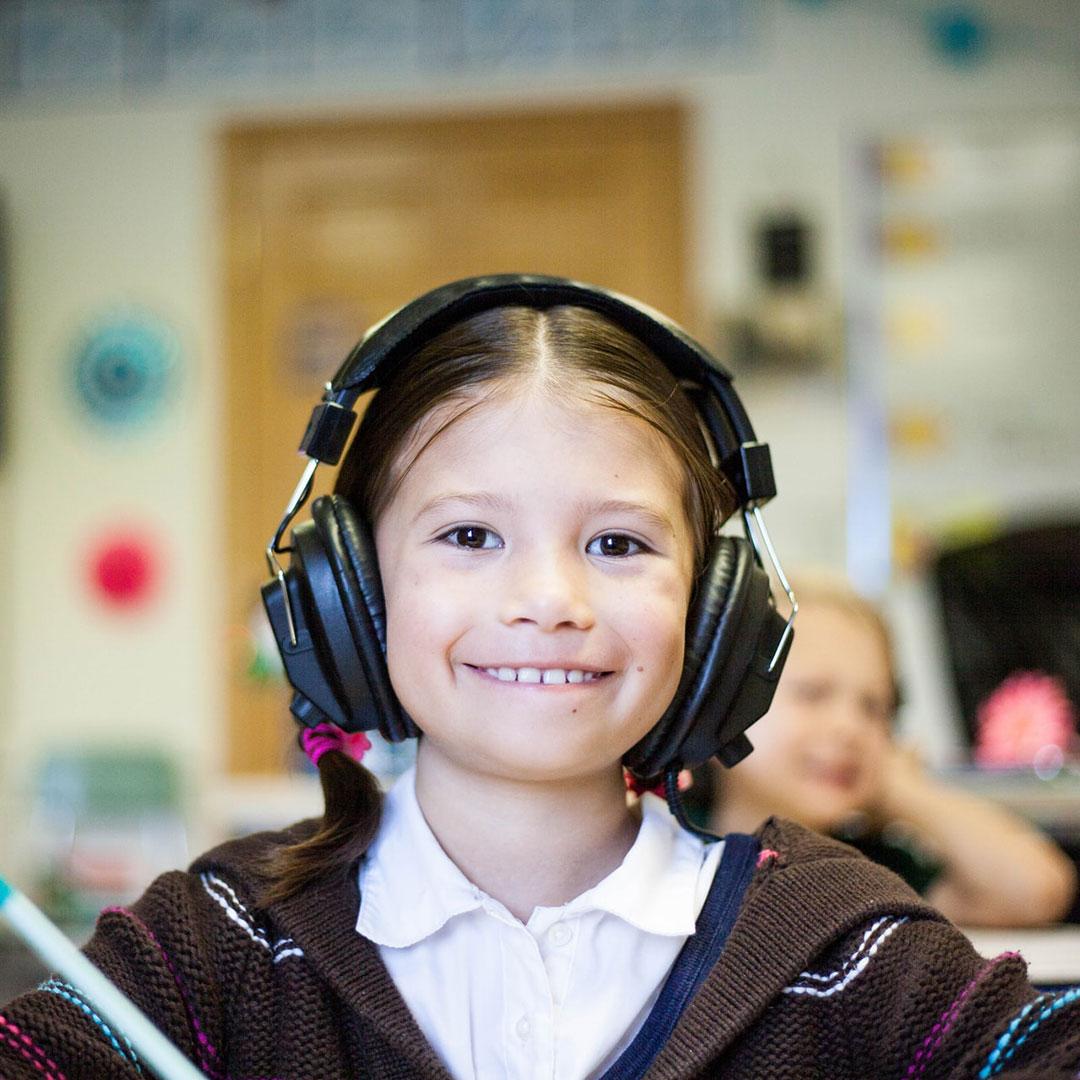 Ein Mädchen sitzt in der Schule mit Kopfhörer vor ihrem Kindergeburtstag