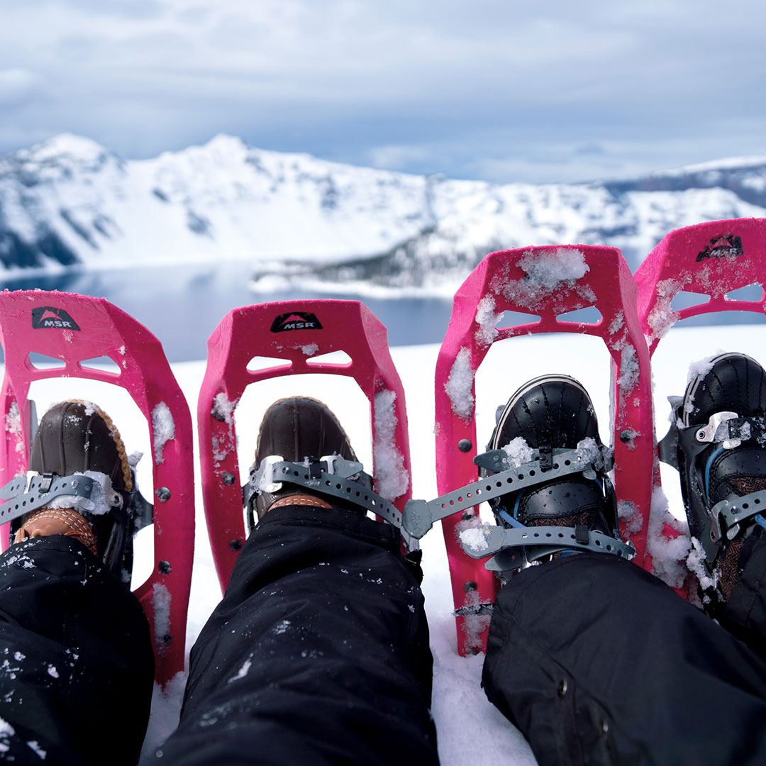 Ein Pärchen beim Picknick mit Rimuss auf einem Berg beim Schneeschuh-Wandern