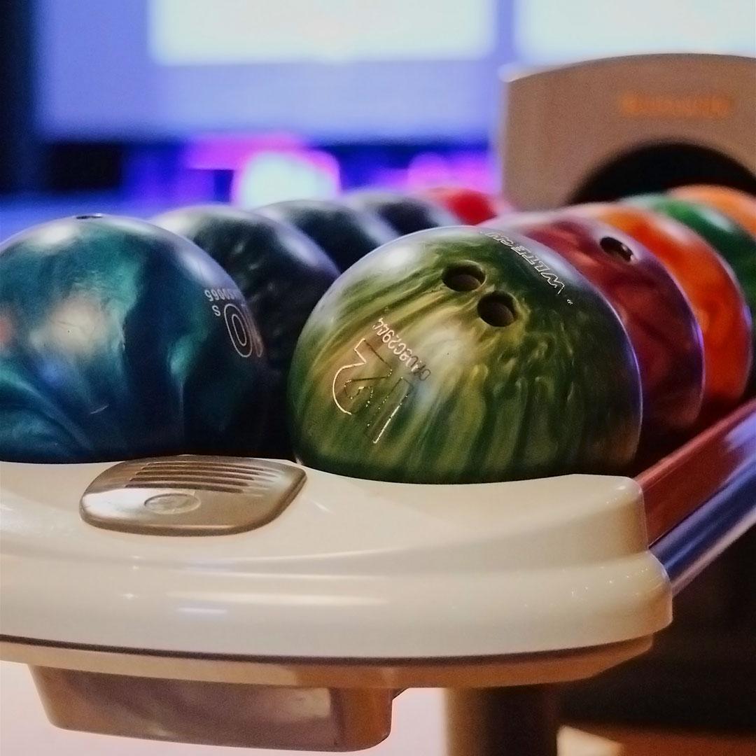Eine Reihe von Bowlingkugeln in einer Bowlinghalle. Ein super Ort um Geburtstag zu feiern