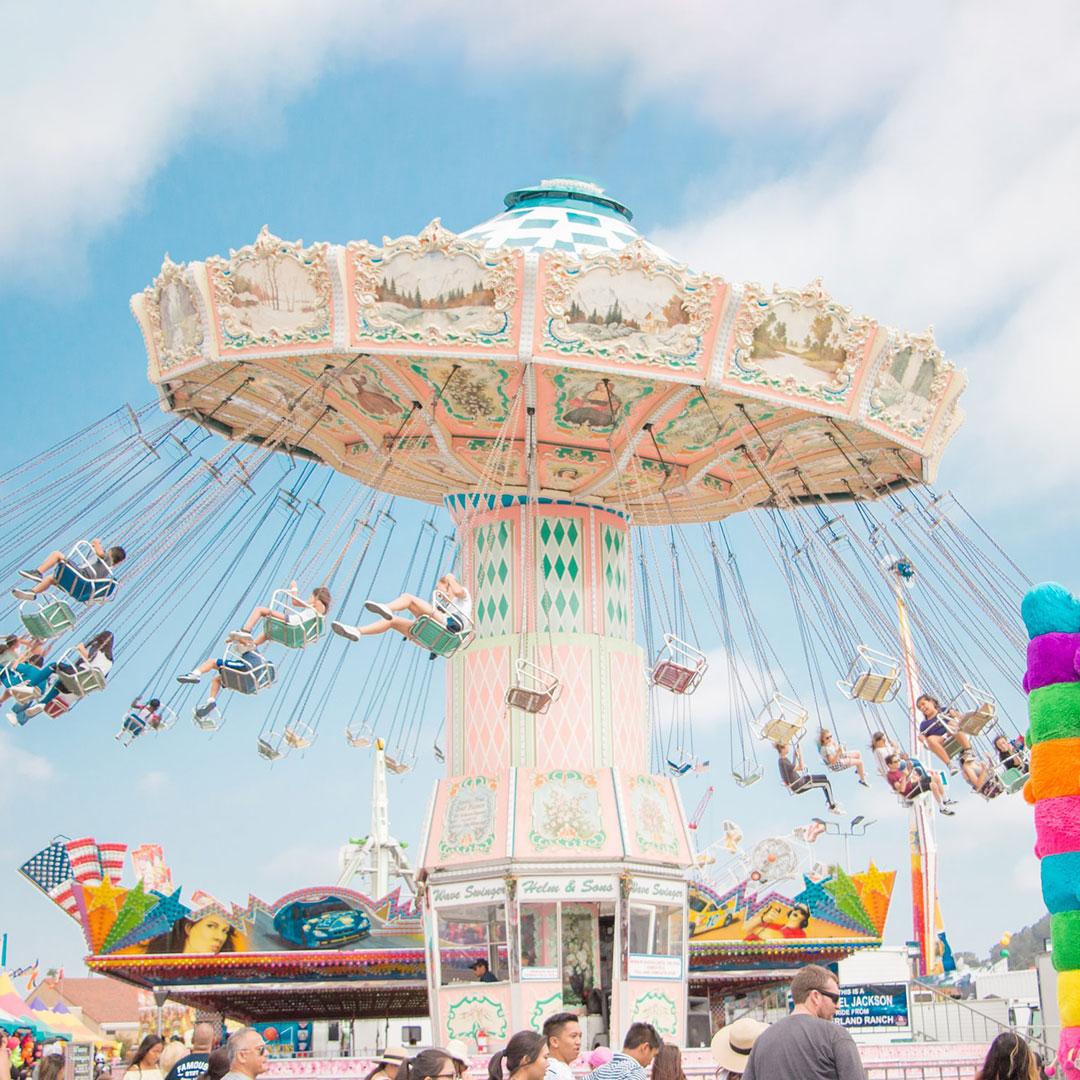 Viele Kinder feiern den Geburtstag in einem Freizeitpark auf einem grossen Karussell