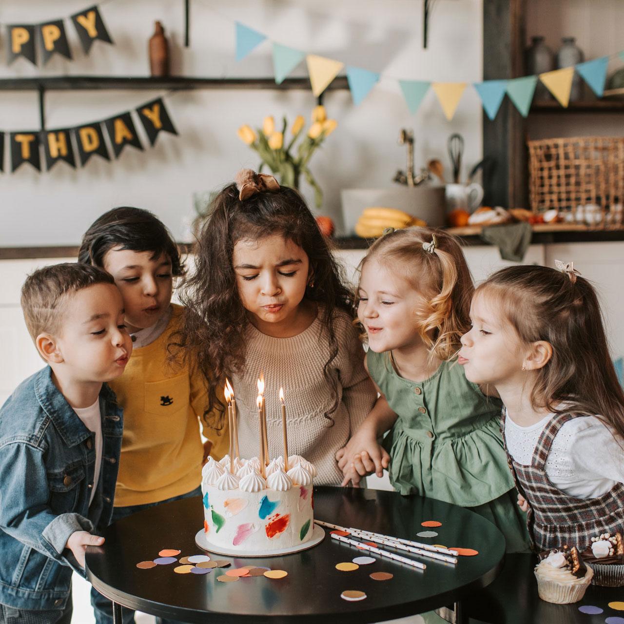 Fünf Kinder feiern zusammen Geburtstag. Das Mädchen in der Mitte bläst gerad die Kerzen auf ihrer Geburtstagstorte aus
