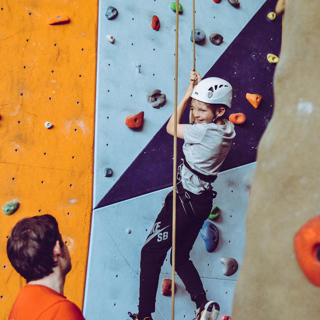 Ein Kind feiert seinen Kindergeburtstag in einer Kletterhalle und hängt an einem Seil in der Kletterwand