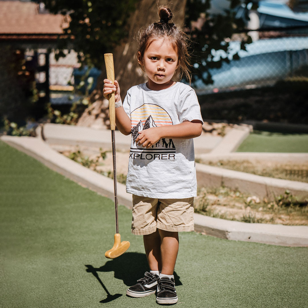 Ein kleines Mädchen feiert seinen Kindergeburtstag auf dem Minigolfplatz