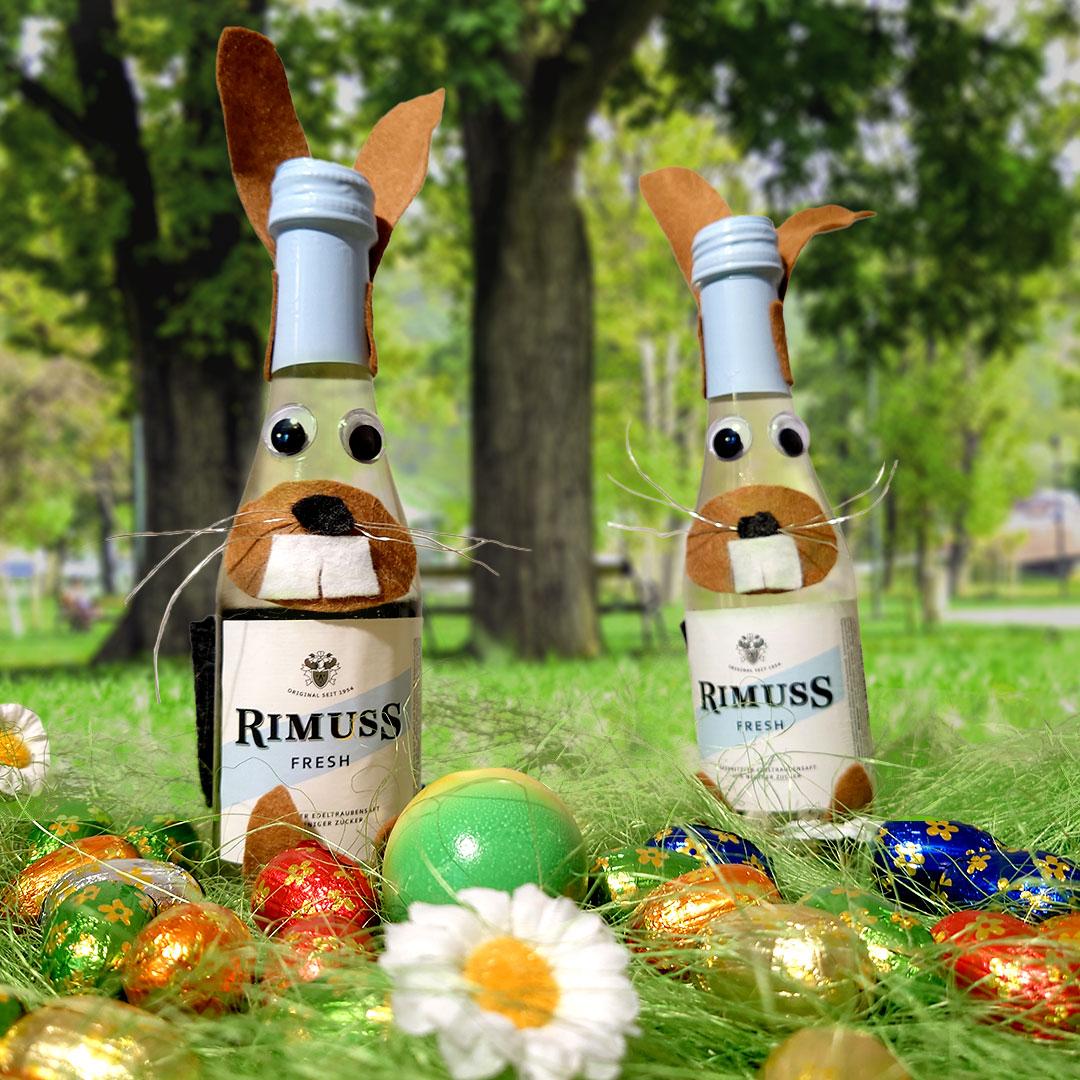 Zwei als Osterhasen verkleidete Rimuss Fresh 20cl Flaschen sitzen auf der Wiese auf einem Park umgeben von Ostereiern. Bereit für den Oster Apero