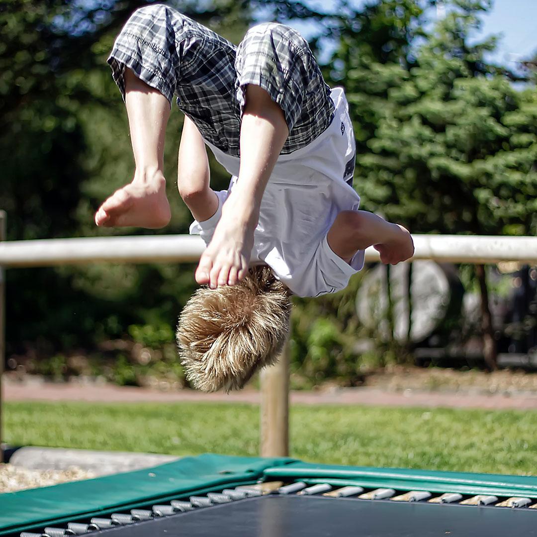 Ein Kind spring an seinem Geburtstag auf einem Trampolin herum und macht einen Rückwerts-Salto