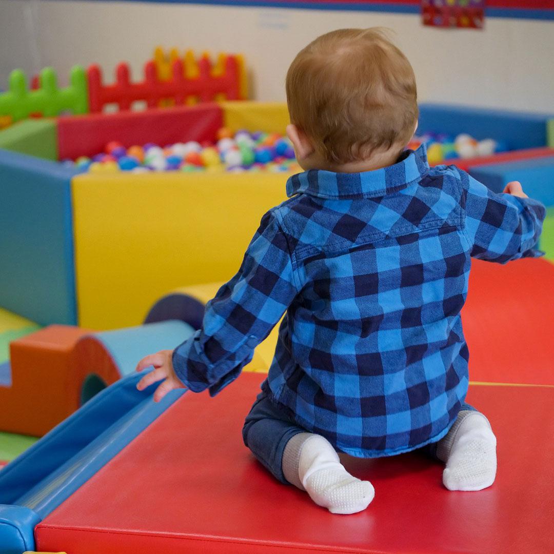 Ein Kind feiert seinen Kindergeburtstag in einem Indoor Spielplatz / Spielzentrum und sitz vor einem Bällebad