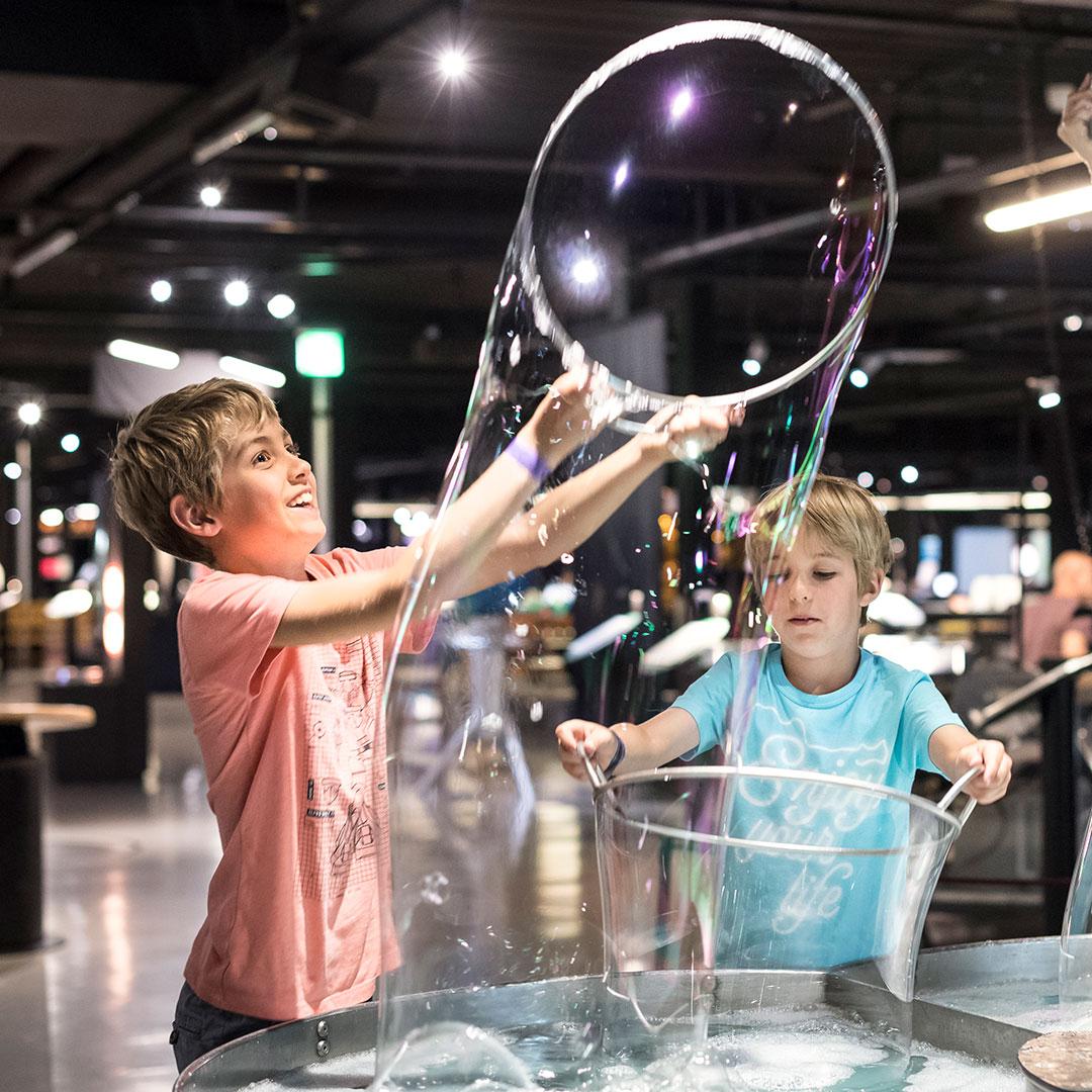 Zwei Kinder spielen beim Kindergeburtstag im Technorama Winterthur mit riesigen Seifenblasen