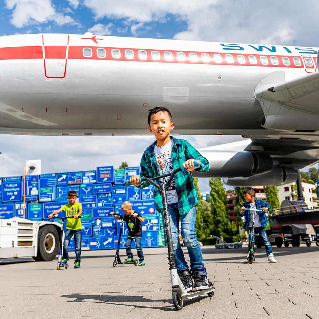 Mehrere Kinder fahren beim Kindergeburtstag im Verkehrshaus Luzern mit Scootern über einen Platz