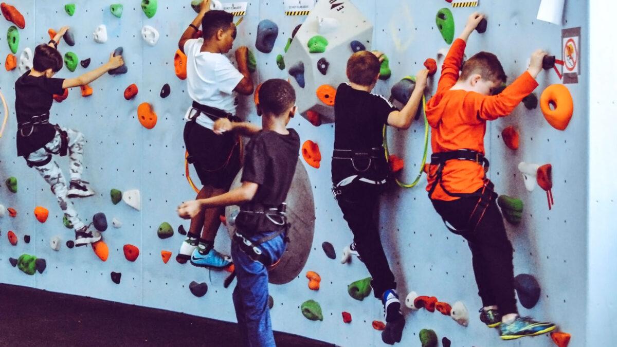 Mehrere Kinder feiern den Kindergeburtstag in einem Ketter Zentrum und klettern eine kleine Kletterwand hinauf