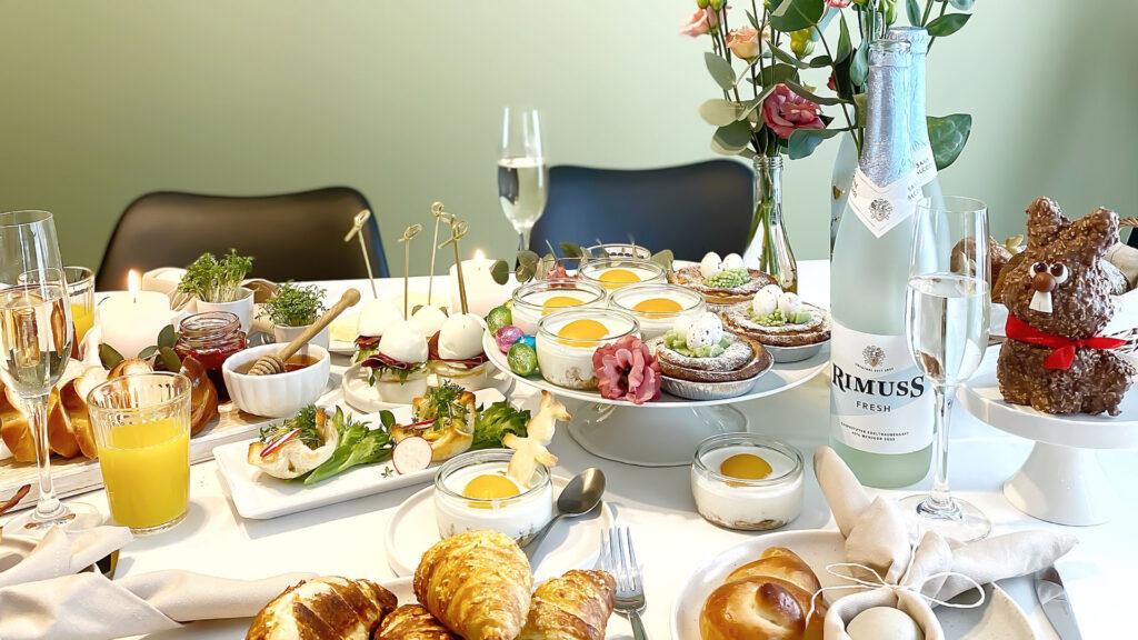 Ein wunderschön hergerichteter Oster Brunch oder Apero mit Brötchen, Gipfeli, Eiern, Orangensaft, Rimuss Fresh und vielen weiteren Leckereien