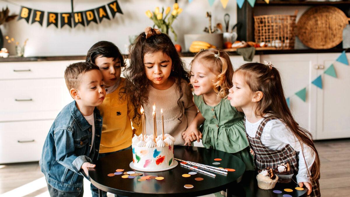 Ein Kindergeburtstag mit fünf Kindern. Das Geburtstagskind bläst gerade die Kerzen auf ihrer Geburtstagstorte aus