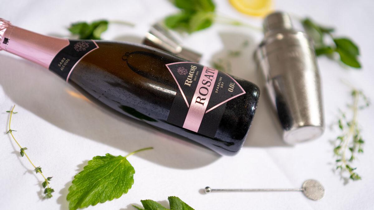 Eine Flasche Rimuss Rosato Dry zwischen Kräuter und Cocktailshaker