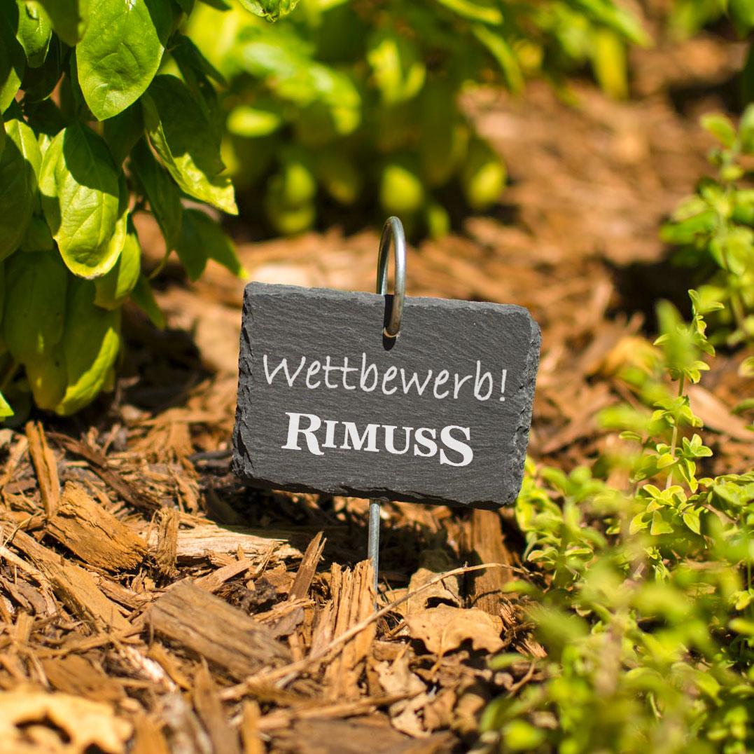 Ein kleinen Steinschild in einem Kräutergarten. Darauf geschrieben: Wettbewerb! Rimuss