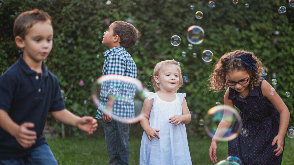 Kinder spielen mit Seifenblasen beim Kinder Geburtstagsfest mit Rimuss