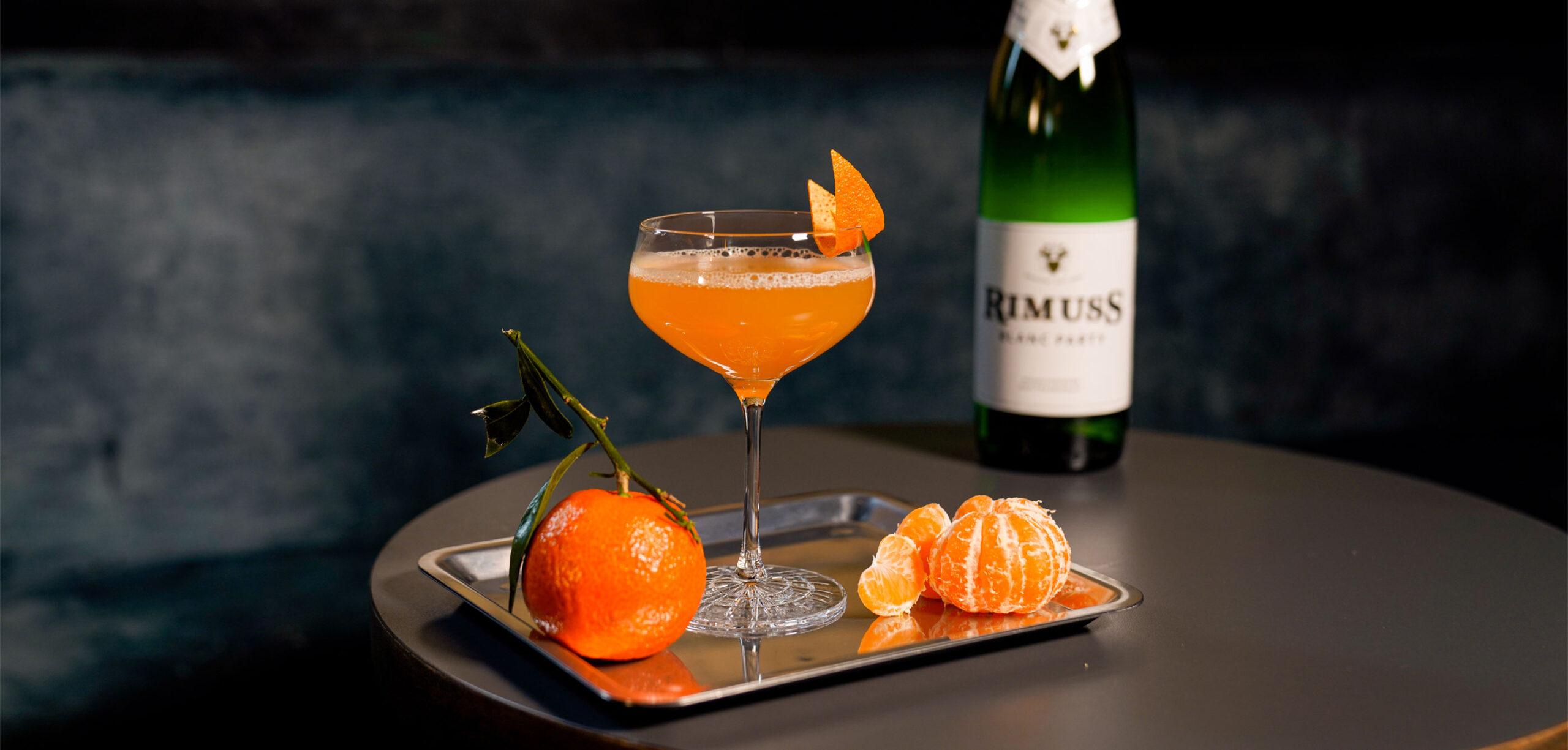Der coole Mocktail mit Rimuss Party auf einem kleinen Bartisch mit Mandarinen