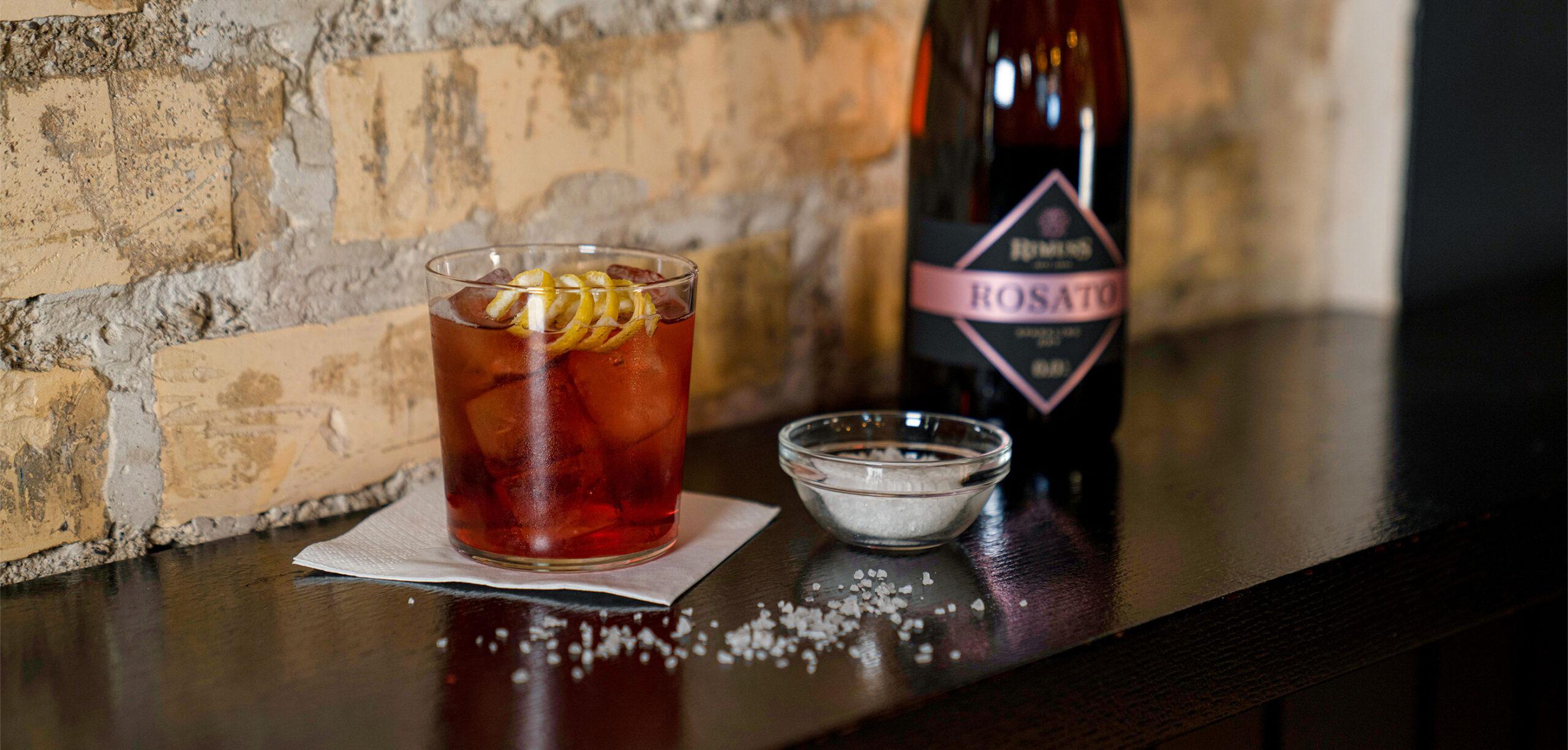 Der coole alkoholfreie Cocktail Cold'n'Dry auf einem Bartisch mit Rimuss Rosato Dry und einer kleinen Schale mit Salz